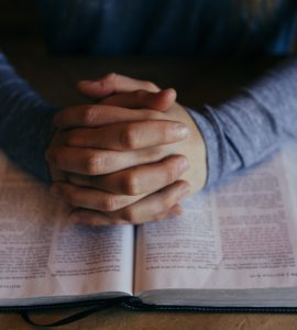 Hands pray on bible