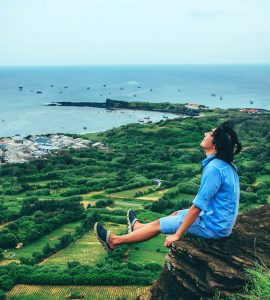 young-man-sitting-on-cliff-enjoying-freedom-in-nature
