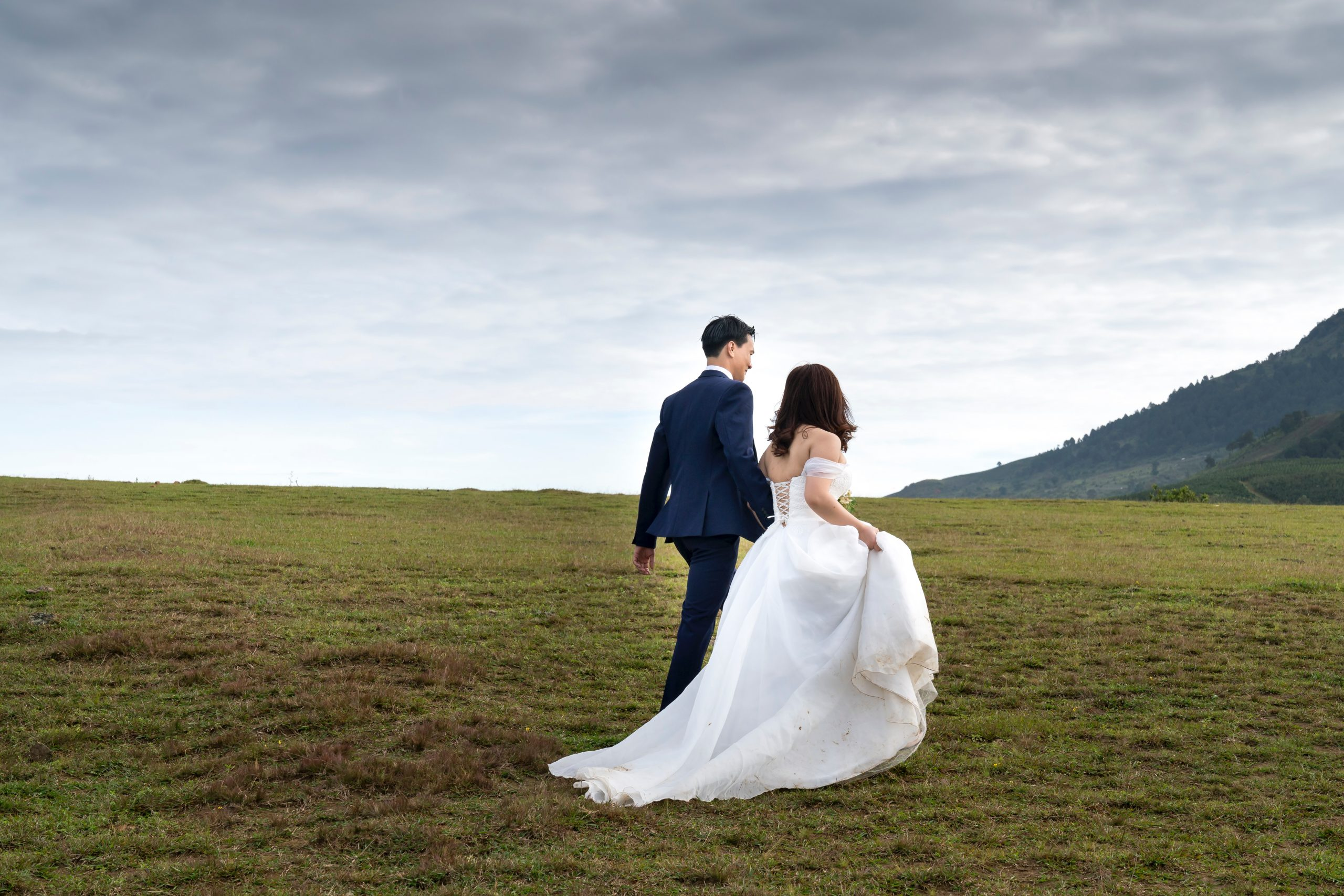 interracial-couple-bride-groom-walking-in-their-wedding-outfits